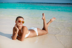 Woman in bikini at tropical beach. Beautiful young woman laying in the sea coast of Maldives. woman on tropical beach at resort with palm tree and bungalows Royalty Free Stock Photos