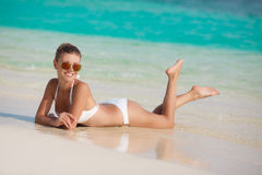 Woman in bikini at tropical beach. Beautiful young woman laying in the sea coast of Maldives. woman on tropical beach at resort with palm tree and bungalows Royalty Free Stock Photography