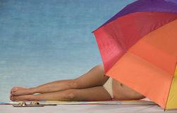 Woman in bikini under beach umbrella. Royalty Free Stock Photos