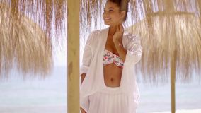 Woman in bikini and under umbrella at beach. Single happy young woman in bikini top and white robe standing under umbrella surrounded by ocean water in stock footage