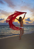 Woman in a bikini walking on the beach. Blond woman in a bikini walking on the beach at sunrise with a chiffon scarf blowing  in the breeze Royalty Free Stock Photography