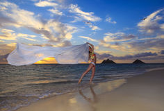 Woman in a bikini walking on the beach. Blond woman in a bikini walking on the beach at sunrise with a chiffon scarf blowing  in the breeze Royalty Free Stock Photo
