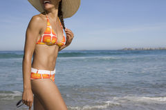Woman In Bikini Walking On Beach. Midsection of young woman in bikini enjoying walk on beach Royalty Free Stock Photography