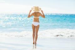 Woman in bikini walking on beach. Rear view of woman in bikini walking on beach Royalty Free Stock Photos