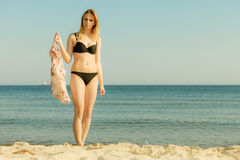 Woman in bikini walking on beach. Relaxing during summertime, traveling, vacation concept. Woman in summer bikini walking on beach near sea, beautiful sunny Royalty Free Stock Image