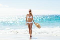 Woman in bikini walking on beach. Young woman in bikini holding hands and walking on beach Royalty Free Stock Images