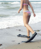 Woman in bikini walking with flippers at the beach. Closeup of beautiful woman in bikini walking with flippers into the water Stock Images