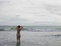 Woman In Bikini Walking In Ocean. Rear view of a woman in bikini walking in the ocean Stock Image
