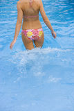 Woman in bikini walking in swimming pool Stock Photos