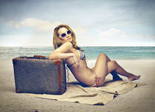Woman at the seaside with her suitcase Royalty Free Stock Images