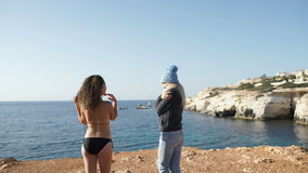Woman in bikini with woman in warm clothes in front of blue ocean. Two young girls comes to the precipice over the ocean. Young brunette in bikini and cute stock footage
