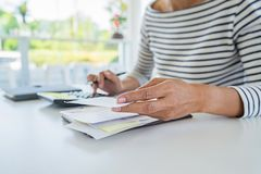 Woman with bills and calculator. Woman using calculator to calculate bills at the table in office. Calculation of costs. Woman with bills and calculator. Woman royalty free stock photography