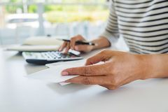 Woman with bills and calculator. Woman using calculator to calculate bills at the table in office. Calculation of costs. Woman with bills and calculator. Woman stock photo