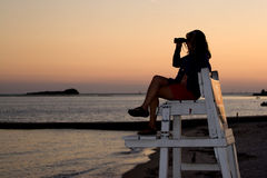 Woman With Binoculars. A silhouette of a woman looking with binoculars at the beach while sitting on a lifeguard chair stock photos