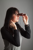 Woman with binoculars. Front lit brunette woman looking via binoculars; gray background Royalty Free Stock Images