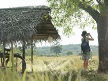 Woman With Binoculars And Bicycle Under Thatched Roof In Field Royalty Free Stock Images