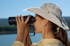 Woman with the binoculars over blue sky Royalty Free Stock Photos