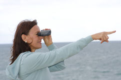Woman with binoculars at seaside. Portrait of an attractive looking mature woman with binoculars, with ocean and clear sky as blurred background and copy space Royalty Free Stock Photos