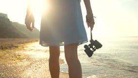 Woman with binoculars at seaside. Legs in dress walking stock video