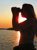 Woman with binoculars watching the sunset Royalty Free Stock Photography