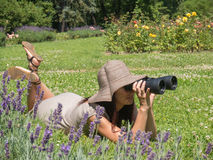 Woman and binoculars. Young woman in hat looking through a binoculars Royalty Free Stock Photography