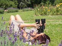 Woman and binoculars. Young woman lying on the green grass and looking through a binoculars Stock Image