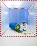 Woman in a biohazard suit testing a spill. Age of green liquid from a drum inside a containment tent Royalty Free Stock Photo