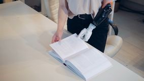 Woman with a bionic arm is turning pages of a book. 4K stock video footage