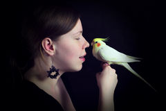 Woman and bird on black background stock images