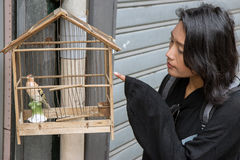 Woman beside a birdcage Royalty Free Stock Photos