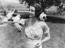 Woman with birds. (All persons depicted are no longer living and no estate exists. Supplier grants that there will be no model release issues Stock Photos