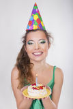 Woman in a Birthday Cap blowing the Candle on Cake Royalty Free Stock Photography