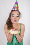 Woman in a Birthday Cap blowing the Candle on Cake Royalty Free Stock Images