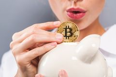 Woman with bitcoin and piggy bank. Woman with bitcoin and a piggy bank on a gray background Royalty Free Stock Photos