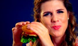 Woman bite burger and winks. Happy student eat sandwich lunch. stock images