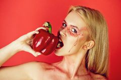 Woman bite paprika on the red background, heart. Woman bite paprika on the red background, sweet bell pepper, heart royalty free stock photos