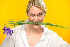 Woman bite spring iris flower between teeth Stock Photo