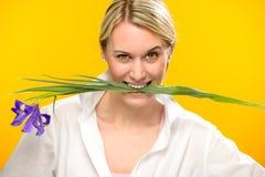 Woman bite spring iris flower between teeth Stock Photo