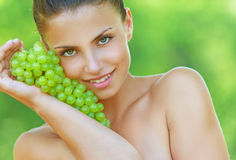 Woman bites off from grape bunches Stock Photos