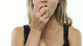 Woman bites peach. Sexy woman eats peach on white stock footage
