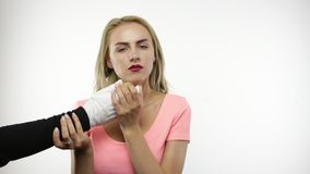 Woman bites pear. Blond woman bites pear from hand with white glove stock footage