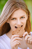 Woman bites piece of bread Royalty Free Stock Images