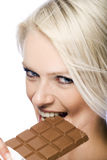 Woman biting a bar of milky chocolate Royalty Free Stock Photography