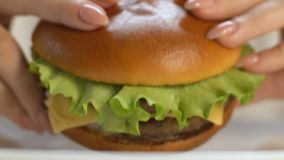 Woman biting big fast food burger, gaining extra weight, saturated fat, closeup