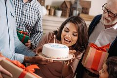 Young woman biting birthday cake presented. By cake stock image