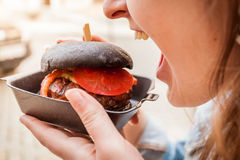 Woman biting black burger with marbled beef Stock Images