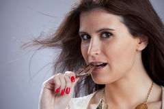 Woman biting chocolate Stock Image