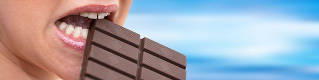 Woman biting in a chocolate bar. Close up of woman biting in a chocolate bar on blurred background stock photos