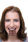 Woman biting in a chocolate tablet Stock Images