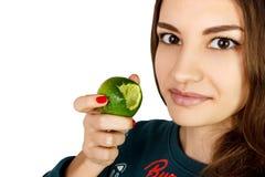 Woman biting citrus fruit lime on white background.  stock image